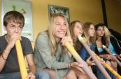 Studenti angličtiny, kteří si zkouší hru na tradiční australský hudební nástroj Didgeridoo, Lexis Noosa Heads, Austrálie